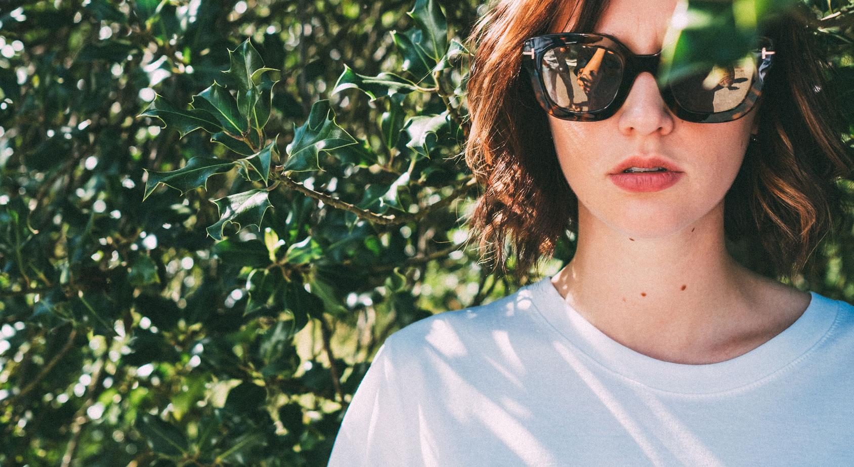 Frau mit Sonnenbrille und Baum im Hintergrund