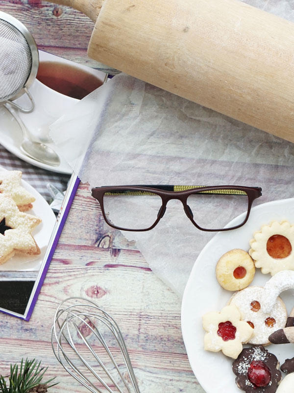 Brille liegt am Tisch neben Weihnachtskeksen