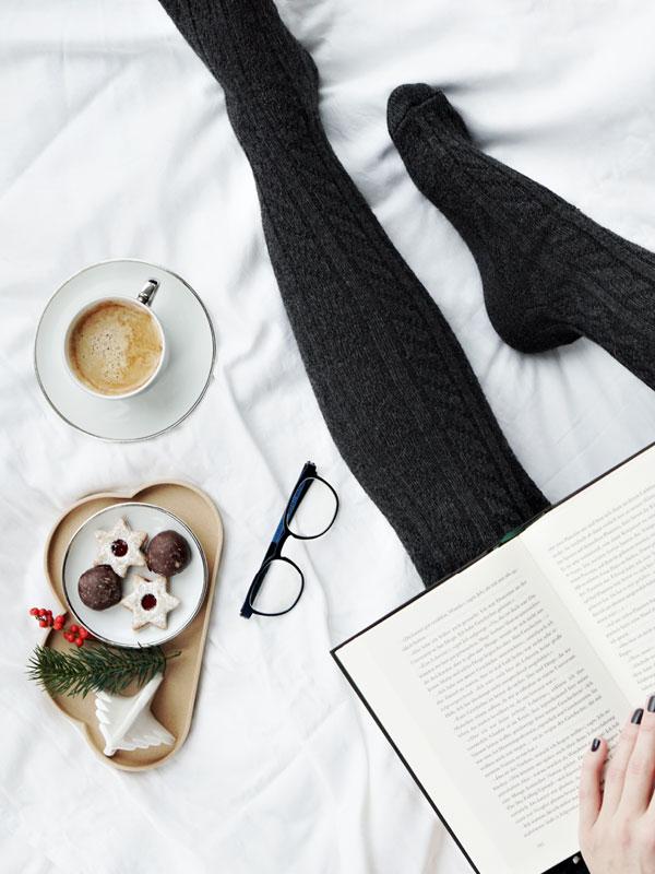 Brille liegt auf weißem Laken neben Keksen und Kaffee